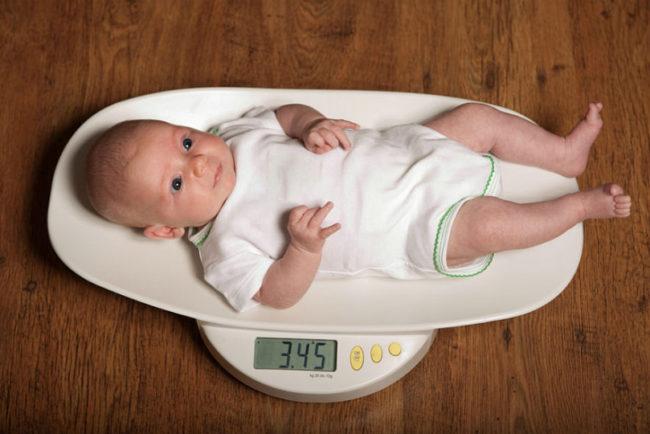 Новорождённый на весах в белой одежде