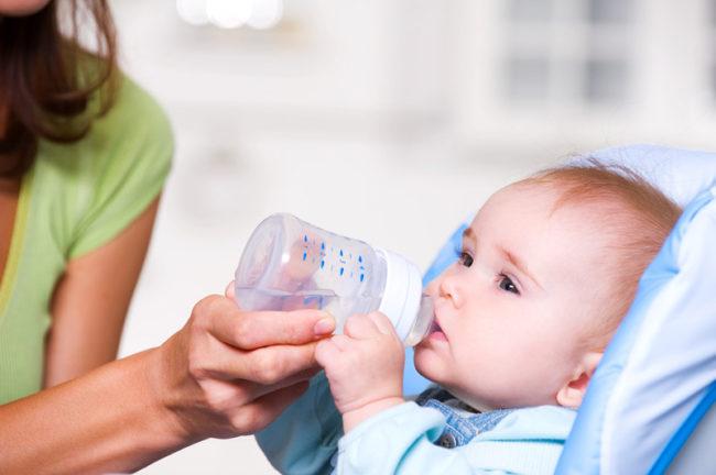 Мама поит новорождённого ребёнка водой из бутылочки