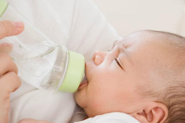 Новорождённый пьёт воду из бутылки