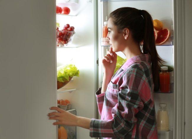 Женщина смотрящая в холодильник