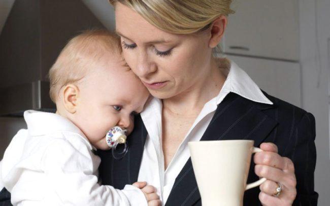 Женщина с младенцем на руках и чашкой кофе