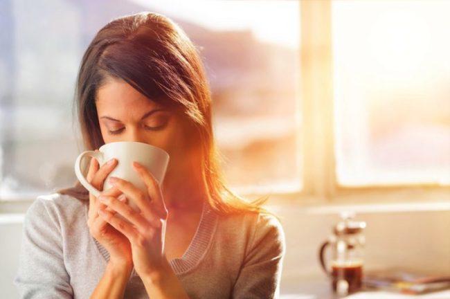 Женщина пьющая кофе из белой чашки
