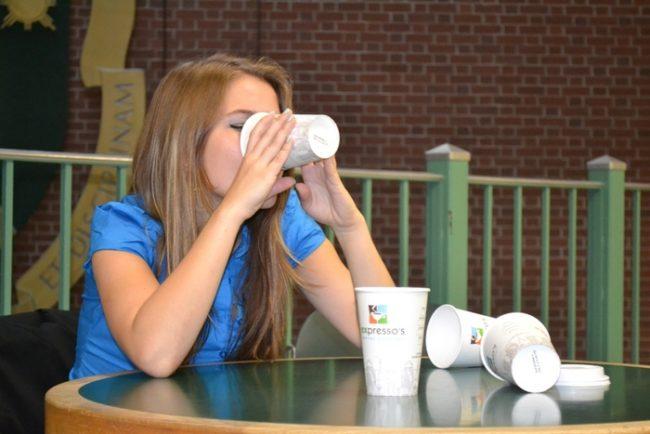 Женщина пьющая много кофе из стаканчиков