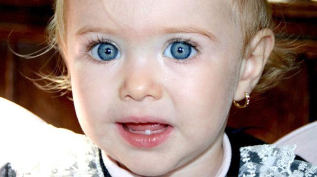 Маленькая девочка с голубыми глазами с одним молочным зубом