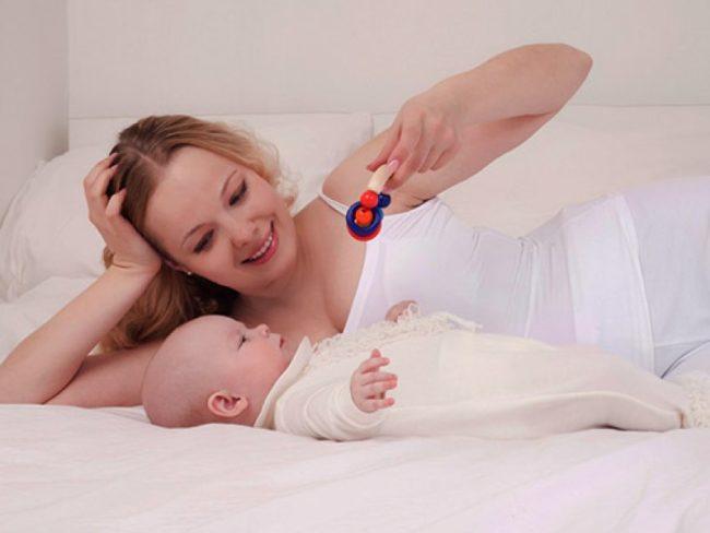 Мама с погремушкой и новорождённый двухмесячный малыш