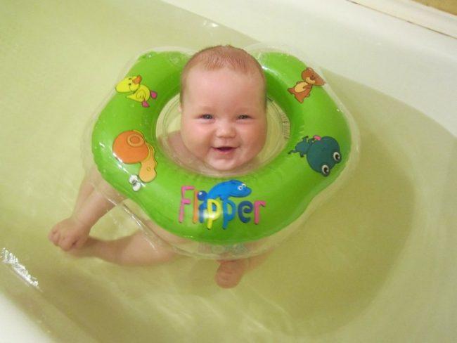 Новорождённый купается в ванной с кругом на шее