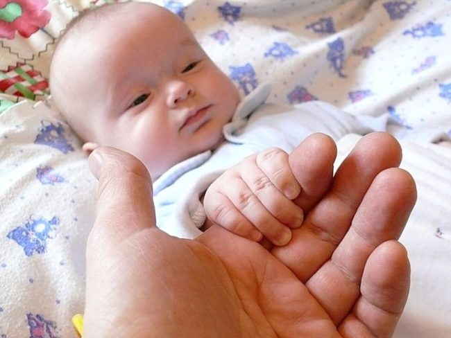 Новорождённый ребёнок даёт ручку родителю