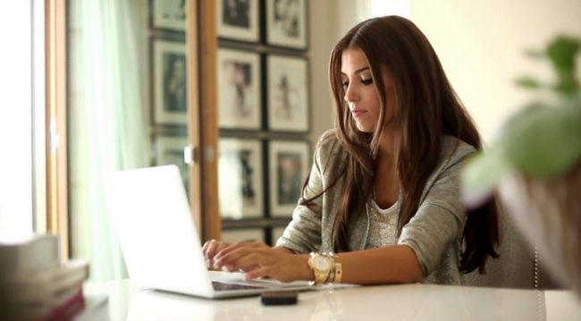 Девушка сидящая за ноутбуком