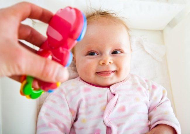 Новорождённый и погремушка