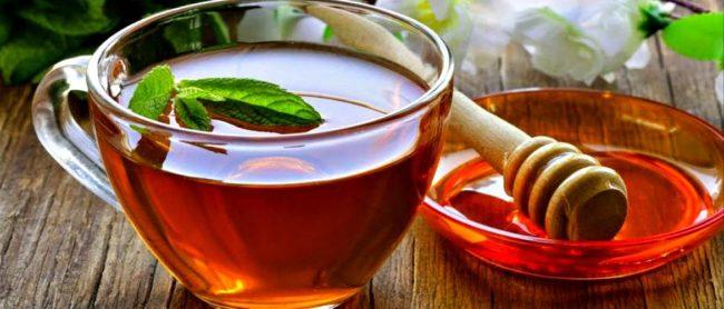 На коричневом столе стоит стеклянная кружка с чаем и стеклянная тарелка с мёдом