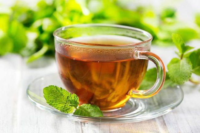 На деревянном столе стеклянная кружка с чаем и мятой