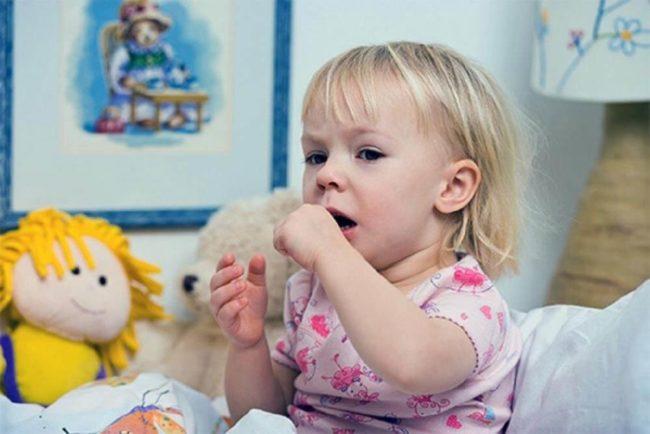 Малышка со светлыми волосами в розовой кофте сидит на кровати и кашляет