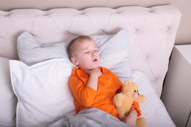 Ребёнок в оранжевой кофте лежит в кровати и держится за горло с игрушкой в руках
