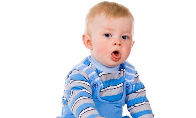 На белом фоне маленький светловолосый мальчик в голубом комбинезоне кашляет