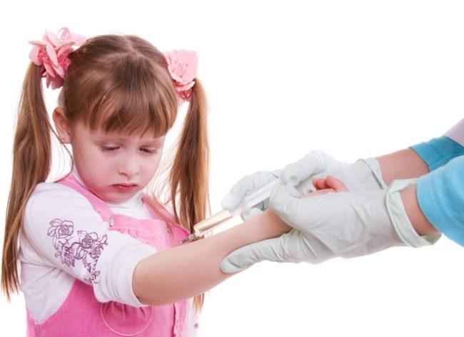 На белом фоне врач делает укол укол девочке с двумя хвостиками