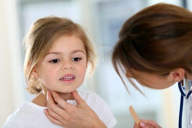 Взрослая женщина проверяет горло маленькой девочки со светлыми волосами и каримиглазами