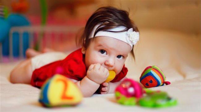 Маленькая девочка с карми глазами и белой повязкой на лбу лежит с игрушкой во рту