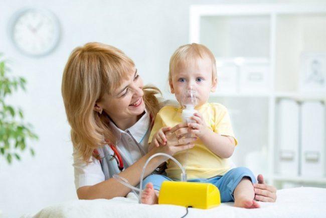 Маленький ребёнок со светлыми волосами в жёлтой футболке с маской на лице сидит у врача