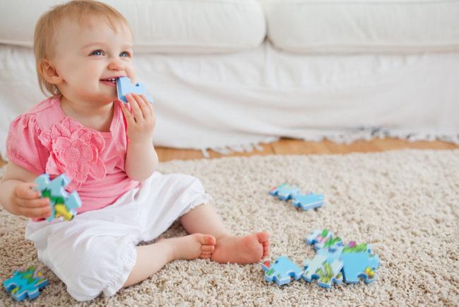 Маленькая девочка в розовой кофте сидит на белом ворсистом ковре с игрушкой в руке