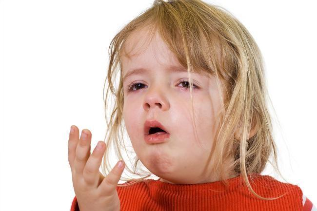 На белом фоне маленькая девочка с русыми волосами в красном свитерете приоткрыла рот