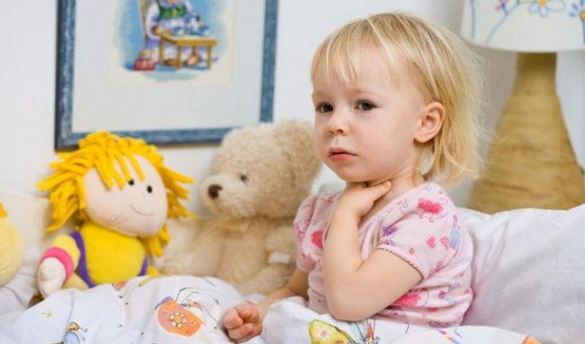 Маленькая девочка со светлыми волосами в розовой майке сидит на кровати и держится за горло
