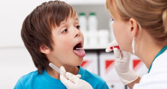 Маленький мальчик с карими глазами в голубой футболке на осмотре у доктора