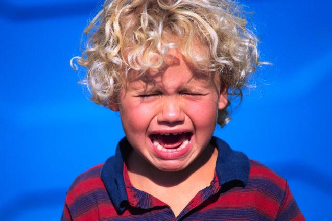 На голубом фоне мальчик с полосатой кофте сильно плачет