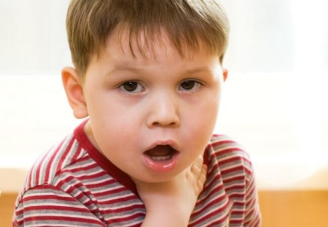 На белом фоне маленький мальчик с карими глазами и в красной футболке держится за горло