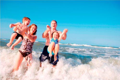 Семья купается в море, дети убегают от волны