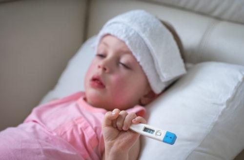 Ребенок лежит в постели с повязкой на голове, в руках у него градусник