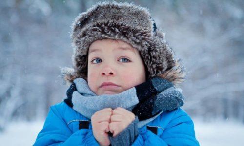 Мальчик замерз на морозе, прижал к себе руки желая согреться