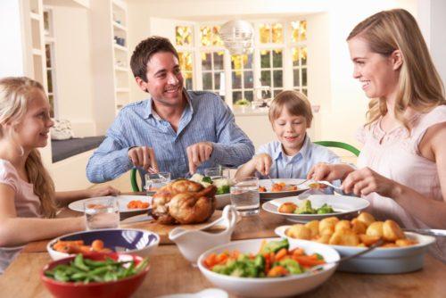 Семья за столом ест вкусный и полезный ужин