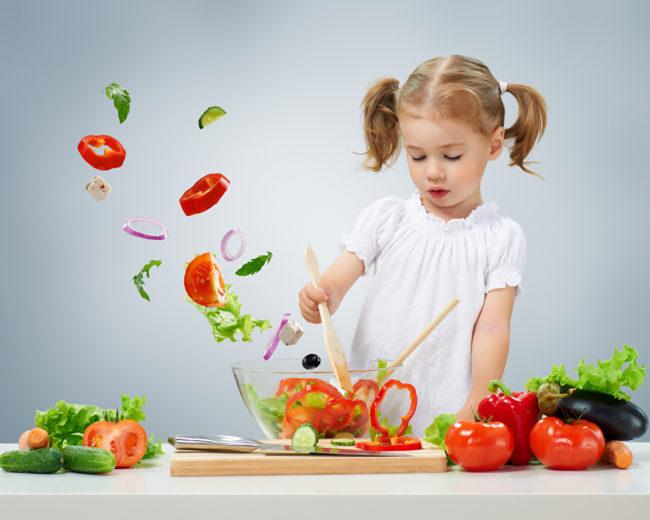 Девочка у стола делает салат из свежих овощей, перемешивает содержимое салатника