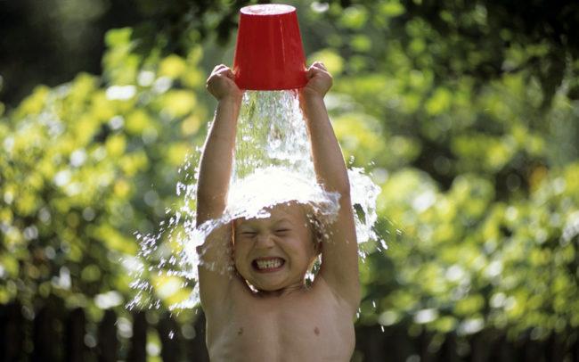 Ребёнок выливает на себя ведро холодной воды для закаливания